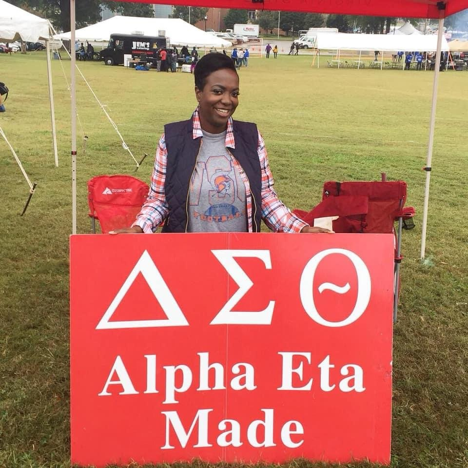Joi Kennedy standing behind a sign with her sorority's name, Delta Sigma Theta, Inc. on it