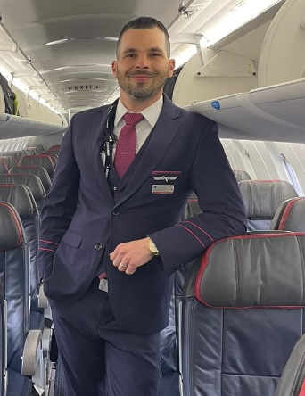 Flight Attendant Adain Bornot Lorenzo smiling in aisle of an empty aircraft leaning on the headrest of a passenger seat with his left elbow