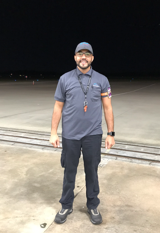Mechanic Carlos Jusino standing in the opening of the hangar with the hangar door open. The night sky is the backdrop behind him.