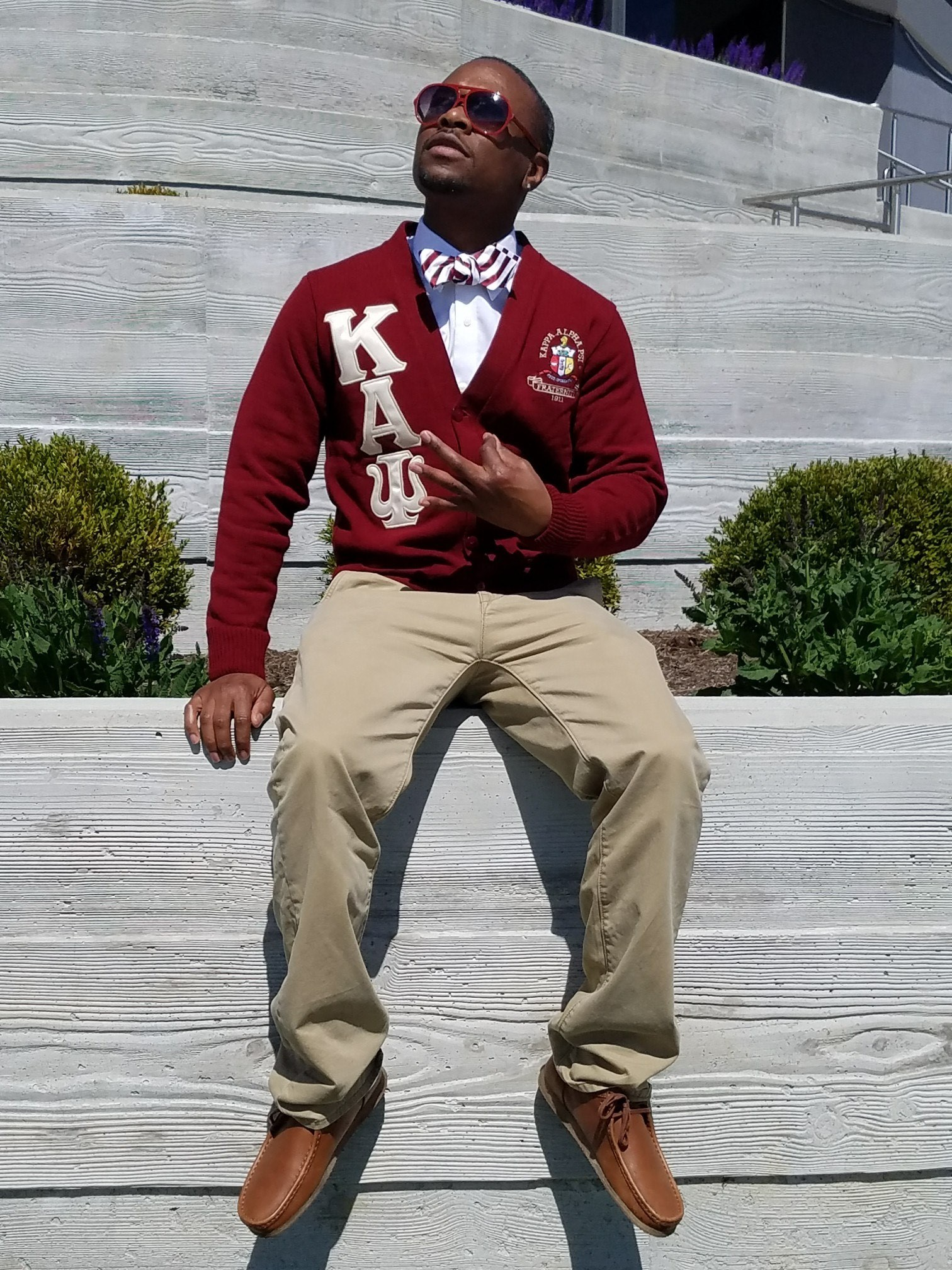 Damian Turner, looking up and into the distance,  connecting thumb and forefinger together, hand gesture use to signify membership of Kappa Alpha Psi, Inc