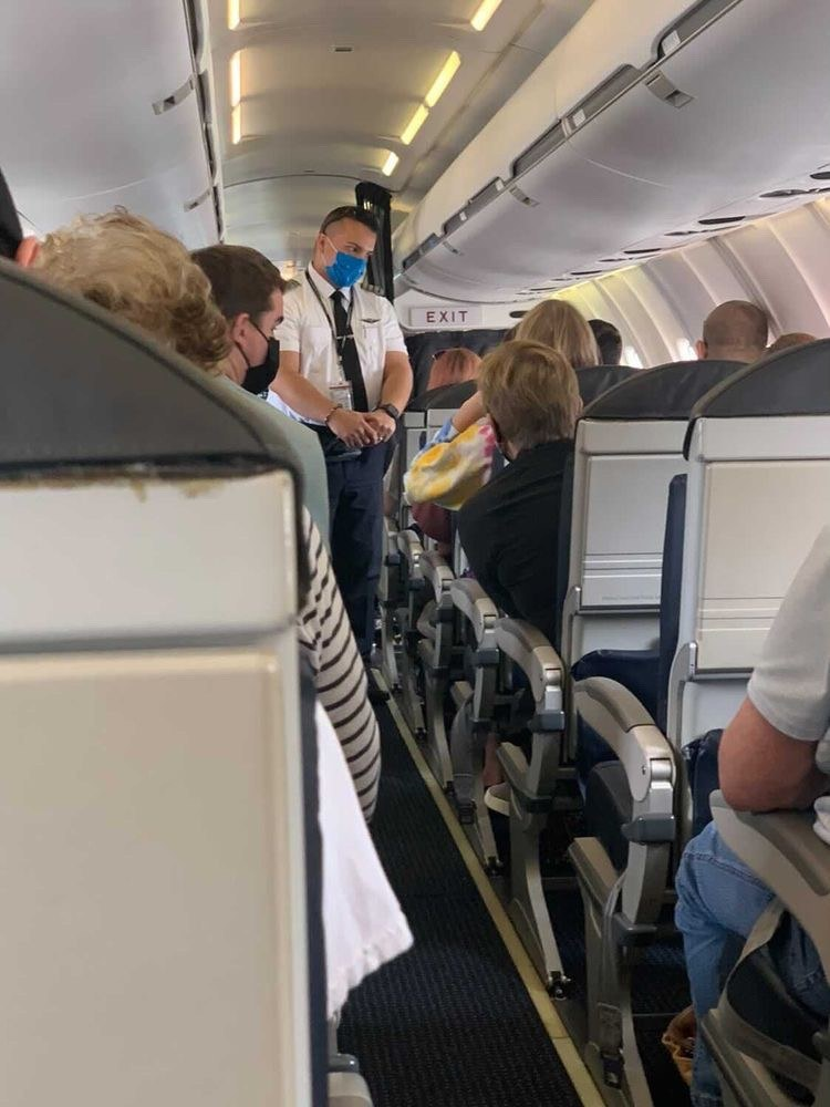 Photo captures Captain Jose O. Torres Lopez standing in the aisle of the PSA aircraft that experienced the 3-hour ground delay. CA Torres Lopez is seen answering questions of customers on board.