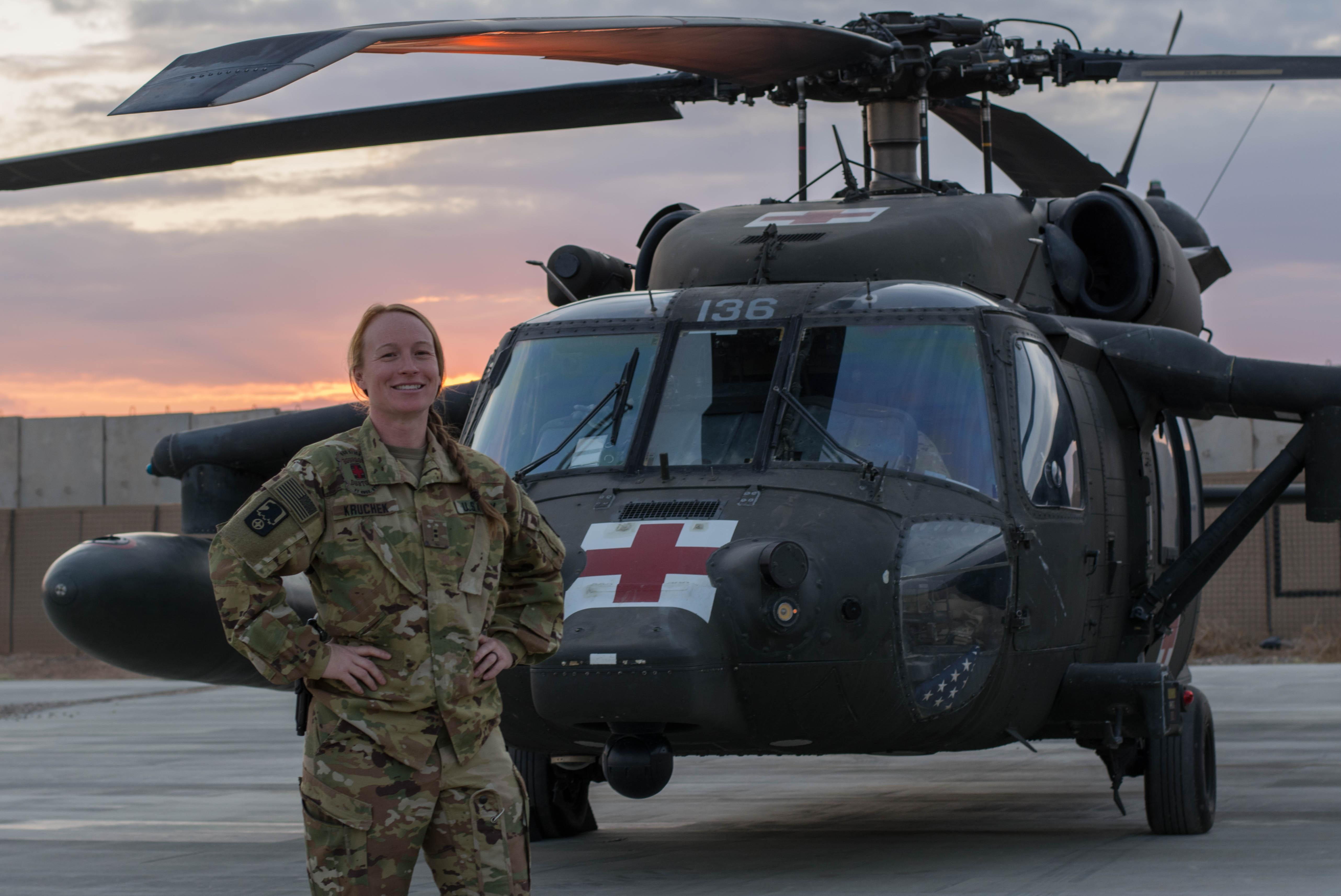 Captain Elizabeth Kruchek in front of military helicopter