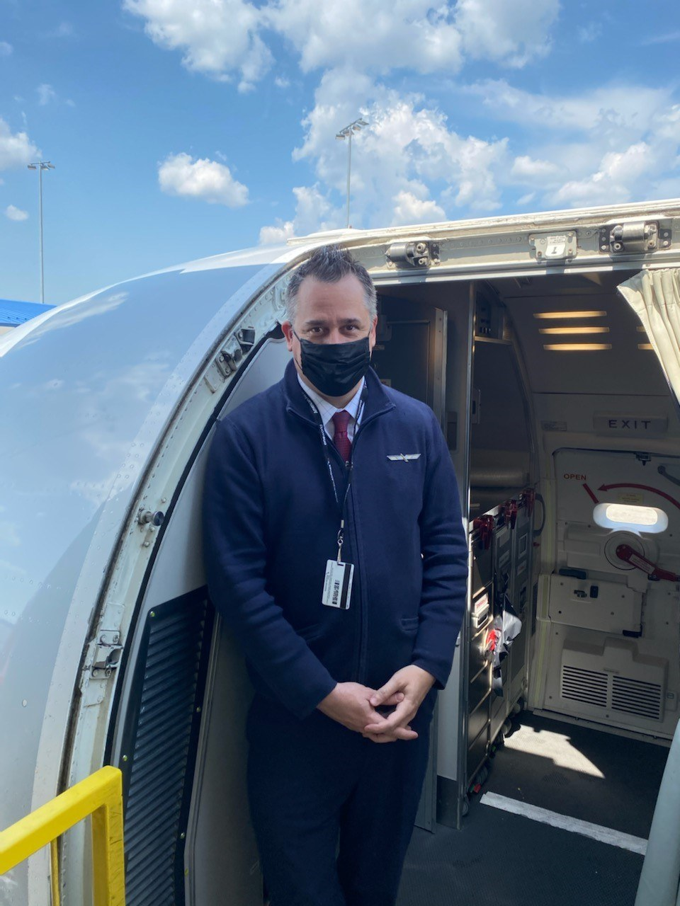 Michael Cruson standing in aircraft doorway with mask on